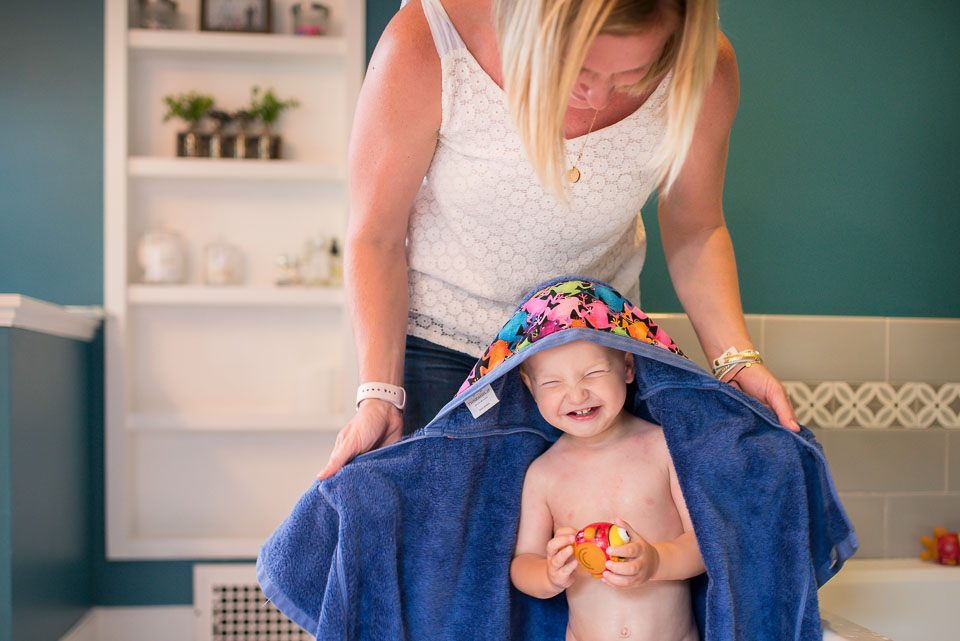 Boy laughs as his mother towels him dry during a Grand Rapids family documentary photography session