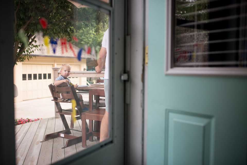 Child in a highchair peers through the door during a documentary family session near Grand Rapids