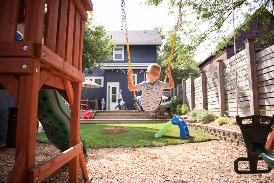 Documentary photography image of a boy swinging over a sandbox while his family approaches in background