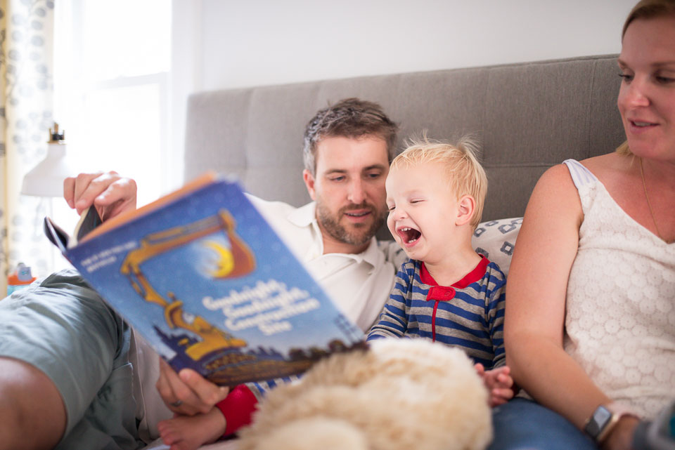 Dad reads book to laughing child while mother looks on during a family photography documentary session