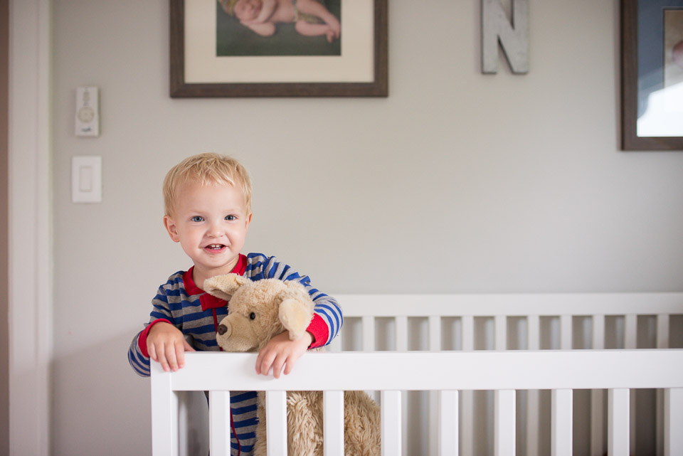 Boy in crib grins at family documentary photographer near Grand Rapids