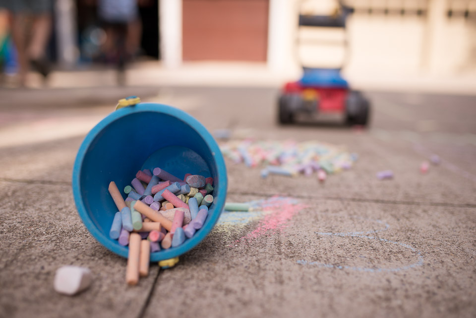 Sidewalk chalk spills from a bucket in this family documentary photography picture