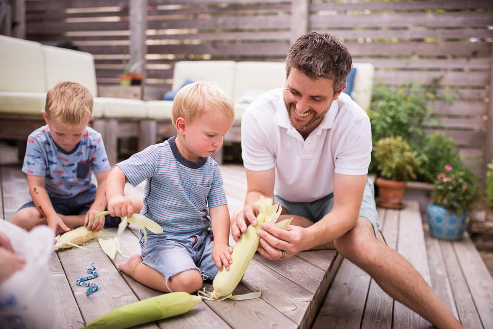 Father shucks sweet corn with sons during a documentary family photography session in East Grand Rapids
