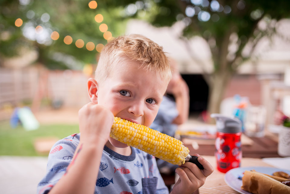 Documentary family photograph of young boy biting into corn on the cob