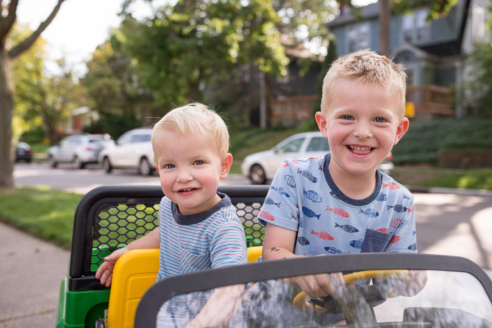 Boys in a motorized car grin at family documentary photographer during East Grand Rapids family walk