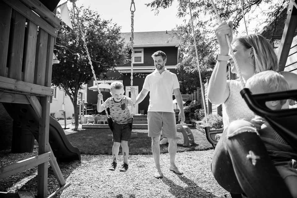 Black and white documentary style family photo of father pushing son on a swing