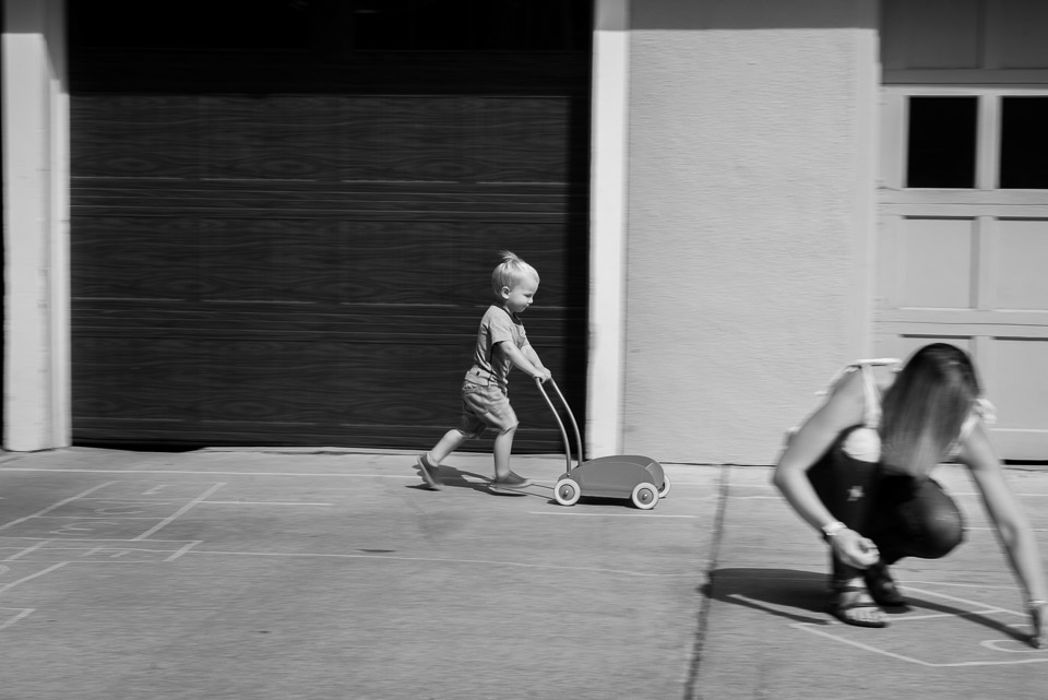 Boy on zooms past mother in this black and white East Grand Rapids documentary photo