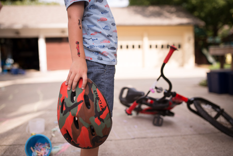 Close up of boys play tattoos and bike helmet during documentary style family session