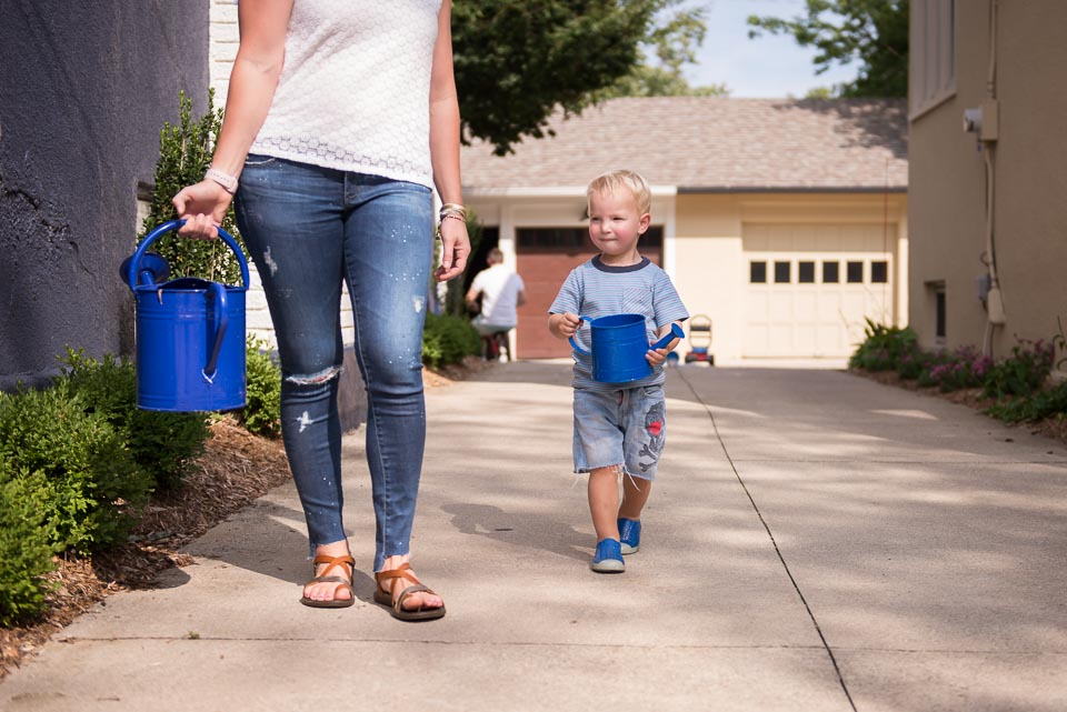 Mother and son carry watering cans during an East Grand Rapids day in the life session