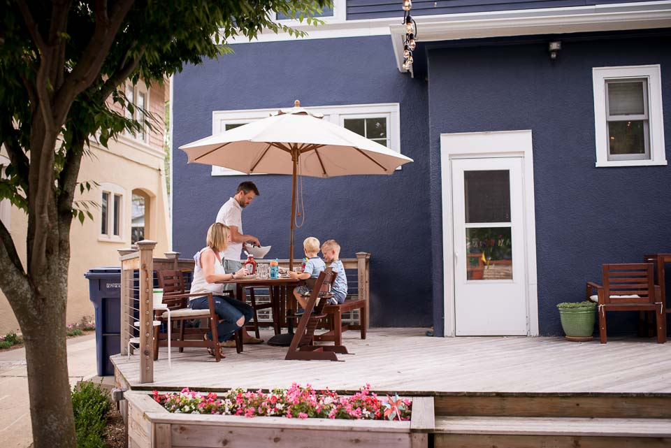 Family dines on deck during a family day in the life photojournalism session near Grand Rapids