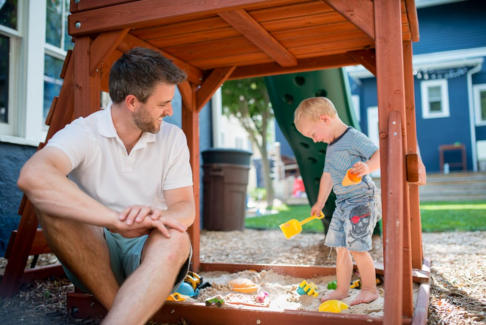 Father and son play in sandbox while a documentary photographer captures day in the life pictures