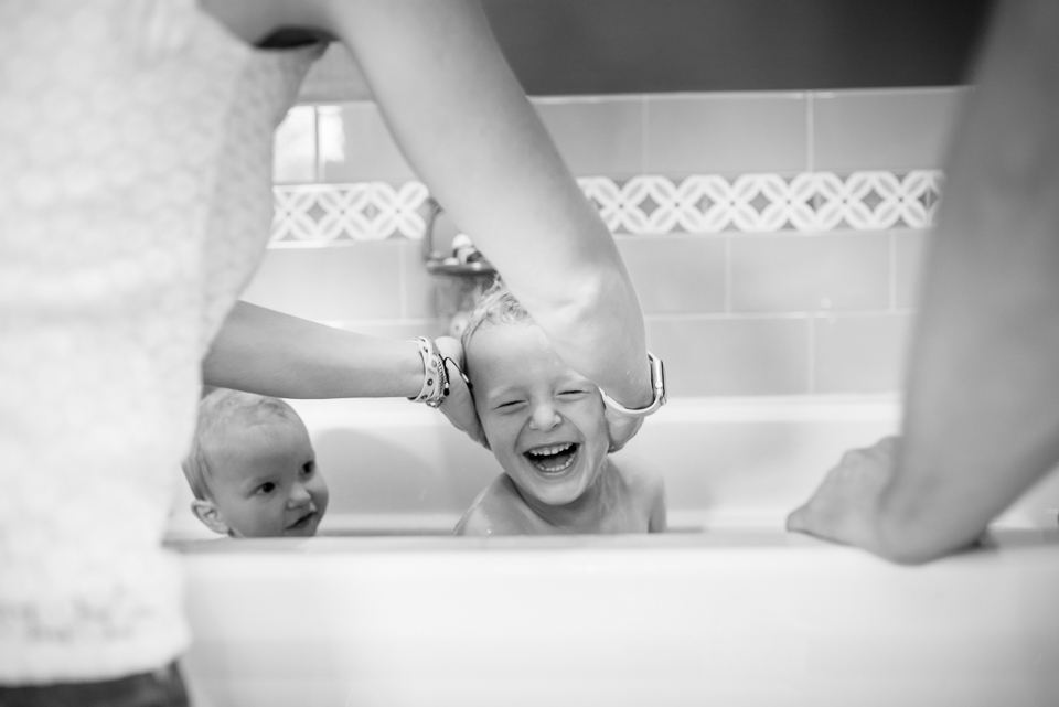 Family documentary photograph of a boy laughing as mother scrubs his head during a bath