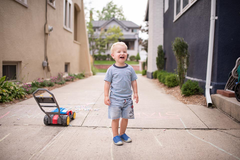 Child laughs joyously as a Grand Rapids family documentary photographer captures his portrait