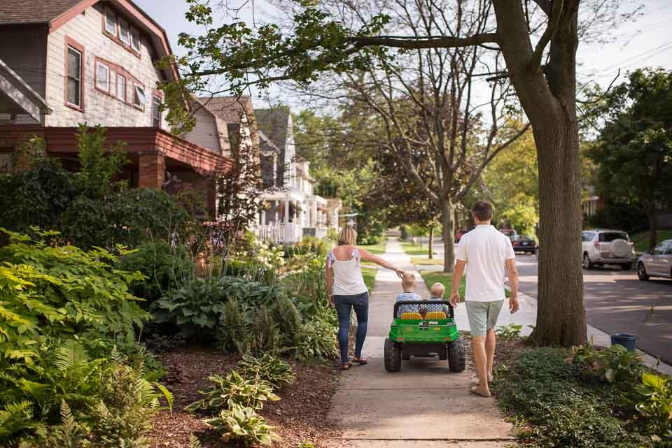 Grand Rapids documentary family photographer image of a family walking through sunny East Grand Rapids neighborhoods