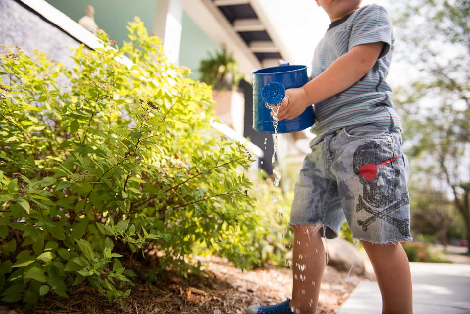 Child spills watering can as he carries it to water plants during a family documentary session