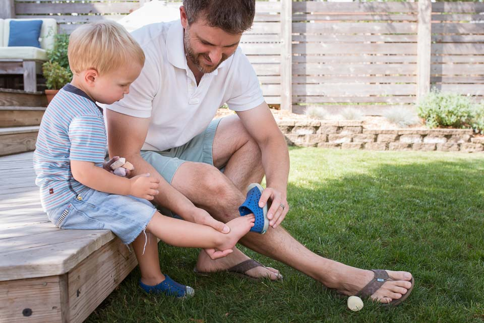 Son watches attentively while father ties his shoes during East Grand Rapids family session