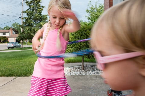 Girl hula hoops and her sister wears sunglasses during a documentary family session near Grand Rapids
