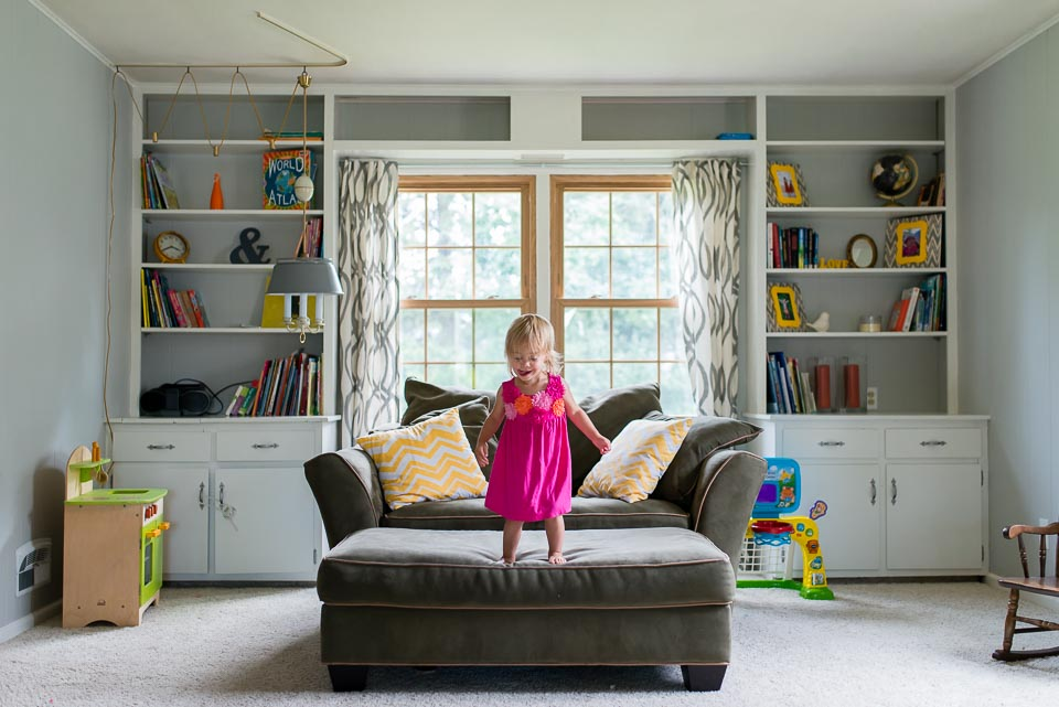 Girl stands poised to jump from couch in Grand Rapids documentary family photography session