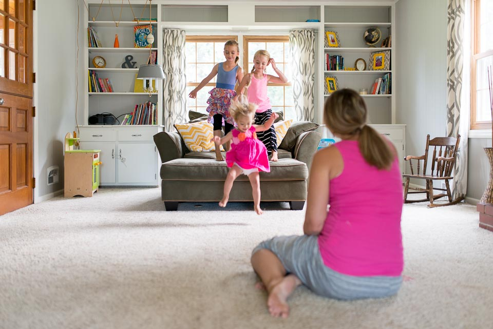 Grand Rapids mother watches her daughters play during documentary family session photography
