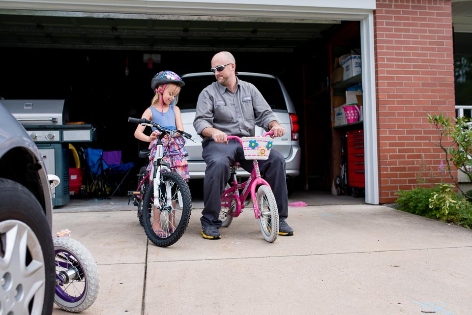 Father and daughter sit on bikes in a Grand Rapids day in the life session