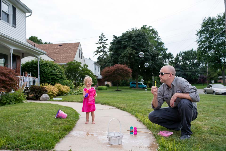 Father blows bubbles with his daughter during family portrait documentary session in Grand Rapids