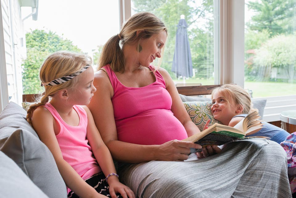 Grand Rapids family documentary image of pregnant mother reading to her children.