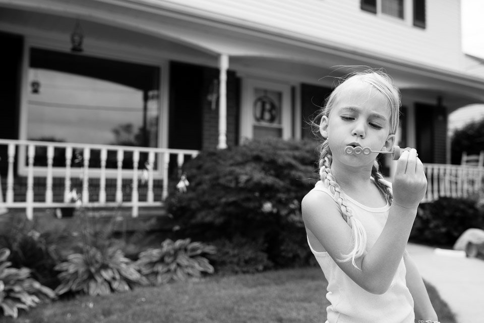 Black and white image of a child blowing bubbles during a family documentary session