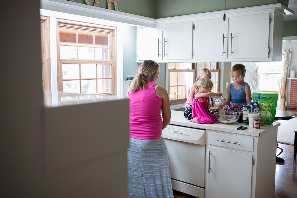 Pregnant mother and three girls bake cookies during a documentary family photography session