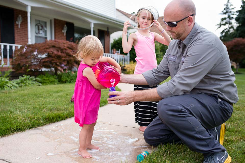 Father in work clothing assists child pouring bubble solution during documentary family photography session