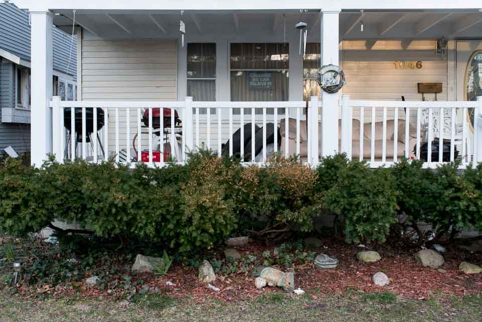 tipped-over-angel-in-front-of-cluttered-porch